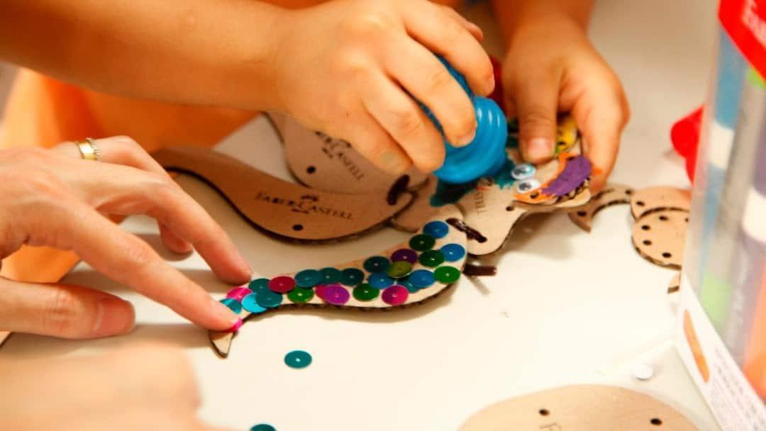 Criança realizando um projeto com tinta, lantejoulas e madeira