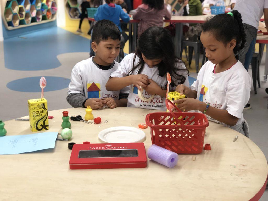 Três crianças planejando projetos e construindo coisas a partir de materiais recicláveis e materiais escolares, parte integrante da metodologia da Aprendizagem Criativa.